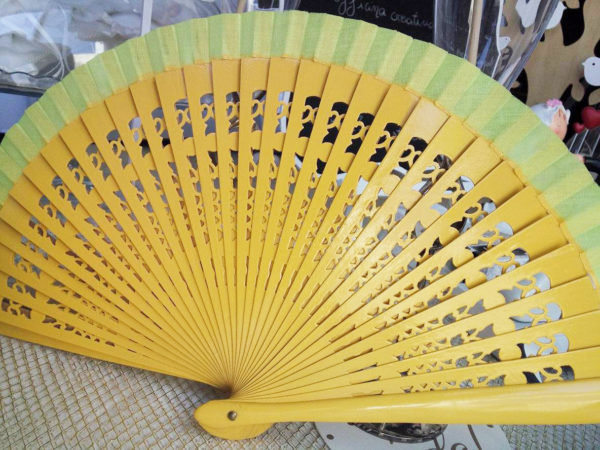 ventaglio in legno intagliato e tessuto giallo